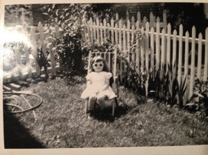 Black and white photo of a young girl wearing sunglasses and posing in a fold-up lawn chair.