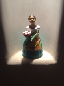 A figure of a hispanic girl offering food