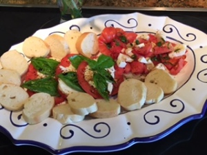 Prepared platter of fresh tomatoes with fresh Basil, Olive Oil & Balsamic Vinegar & French Baguette