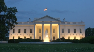 West side of the White House at night flag flying atop and water fountain flowing