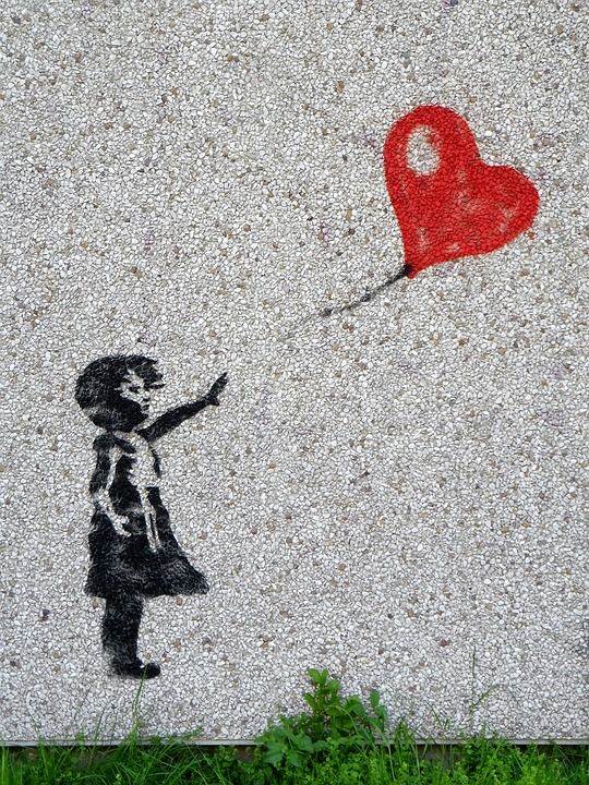 Abstract of a little girl waving goodbye to her heart balloon