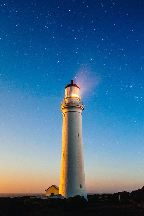 A lighthouse tower projecting its beam of light in the starry night sky