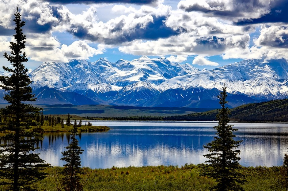 Denali National Park with blue skies, snow capped mountains and calm glacier lake