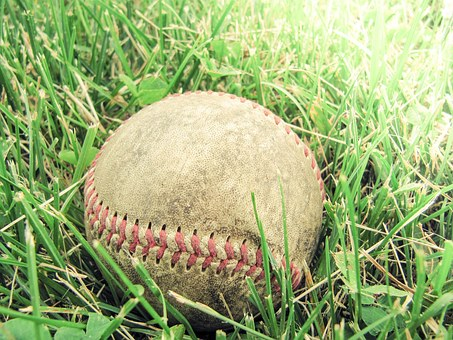 A baseball laying in a grassy field