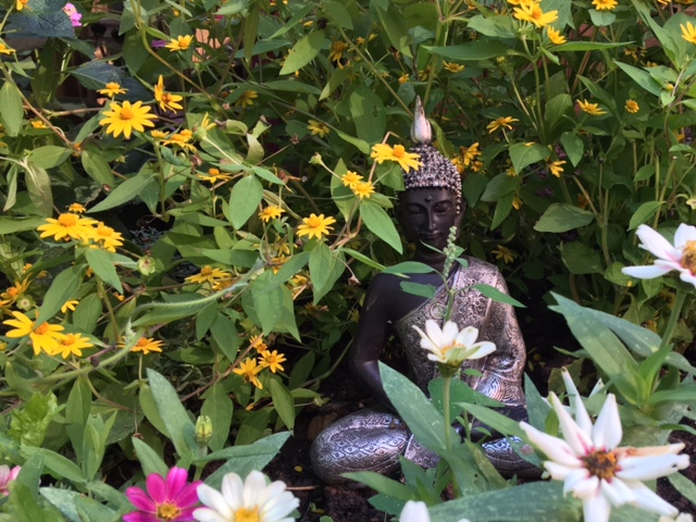 Statue of The Buddha surrounded by flowers in late summer