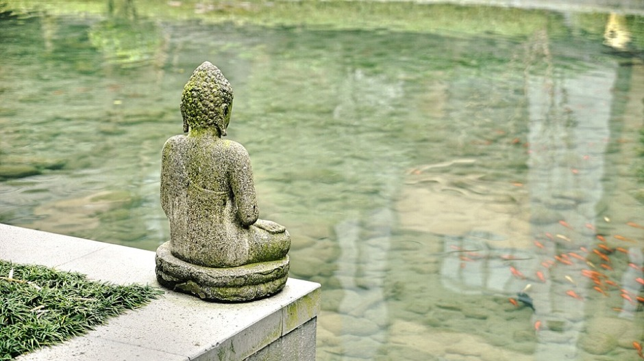 Looking at the back of a Buddha Statue overlooking Koi swimming in a pond