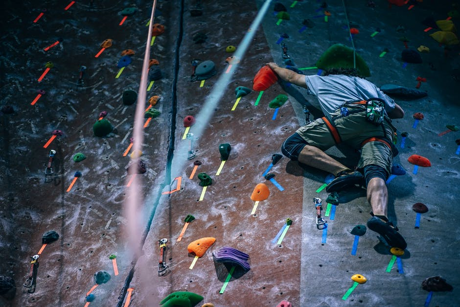 pexels photo of a man climbing a rock wall