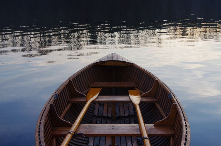 A wooden row boat sitting with quiet oars