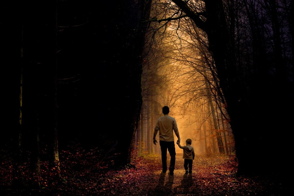 father walking with young son and holding hands walking on a path