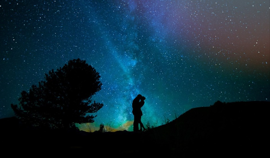 humans embrace with the starry night sky behind them