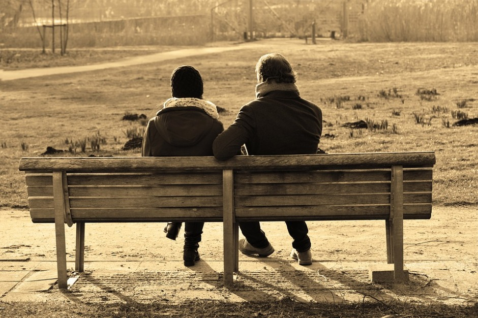 See the backs of two people sitting on a bench