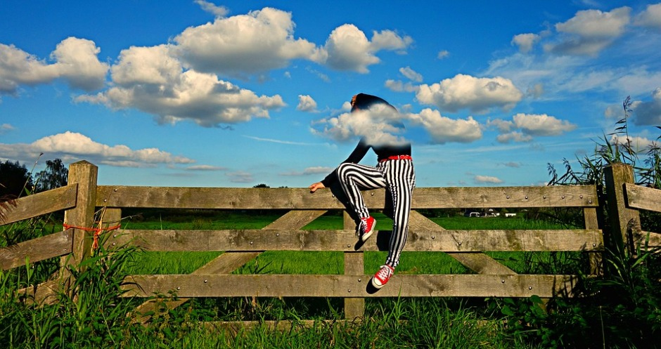 person sitting on a fence