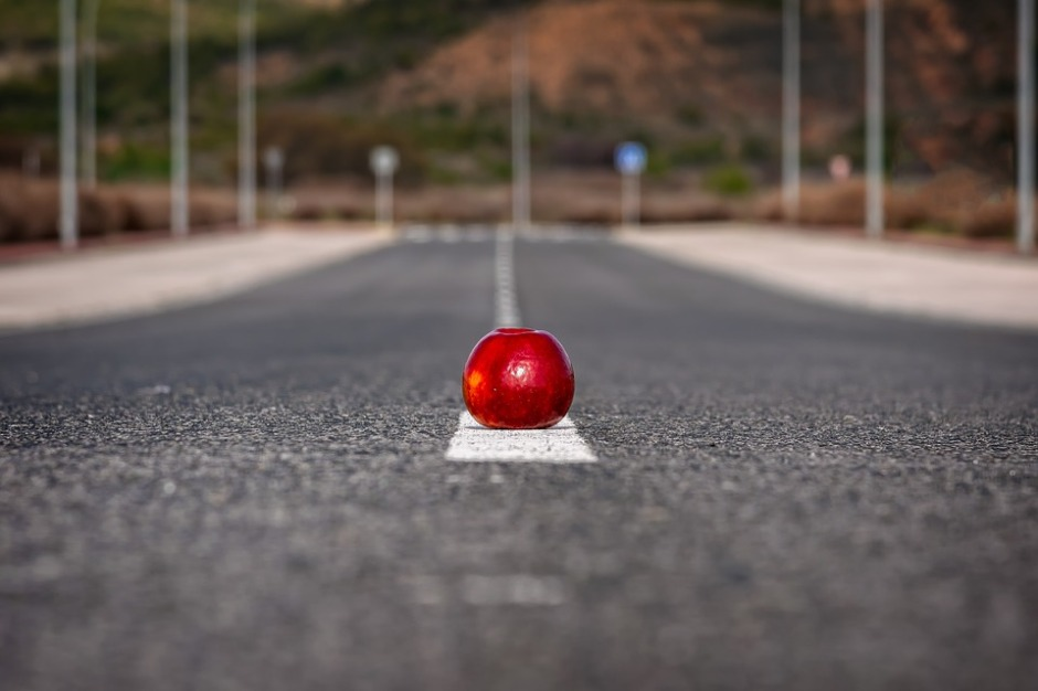 a red apple on the center line on the road