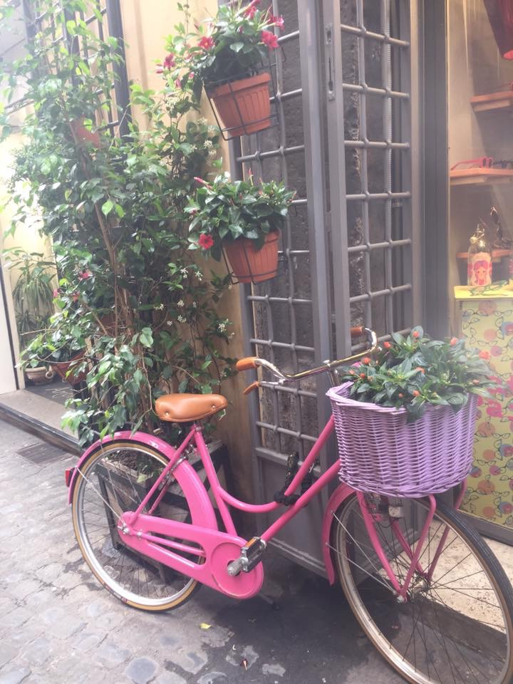 A pink bike with a lilac basket in parked in Tuscany
