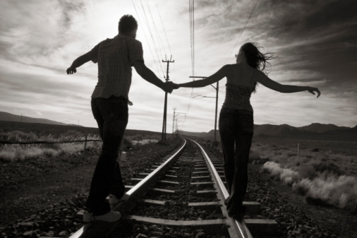 Young couple walking hand in hand on train track, rear view