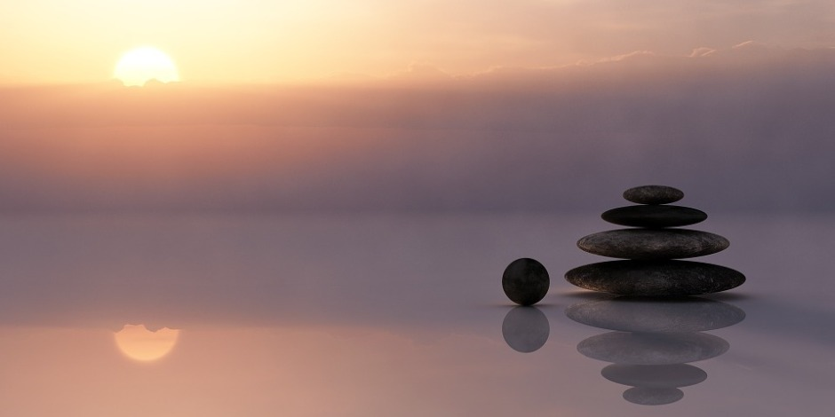 A cairn with a sunrise in in the background