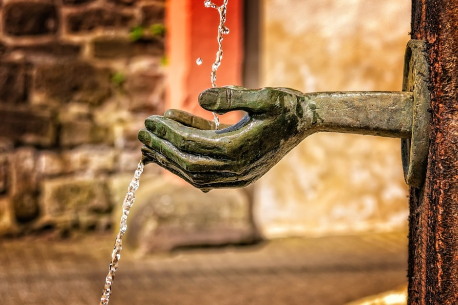 water fountain in the shape of human hands collecting the water