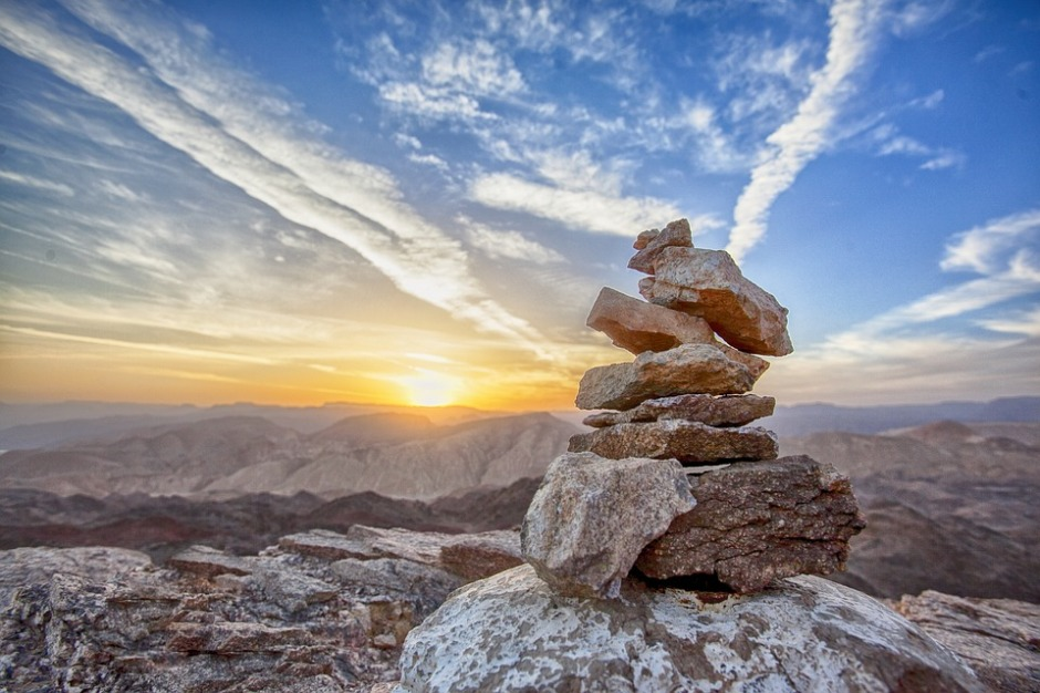 a stone cairn with mountains and sunrise in the background